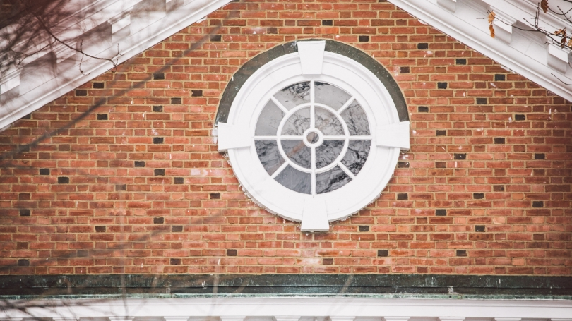 Round white window surrounded by brick